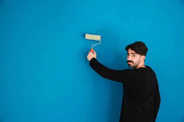 Man peinture mur avec rouleau de peinture