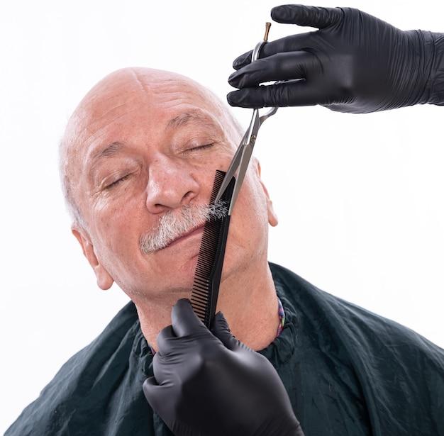 Man pendant le processus de toilettage de la moustache