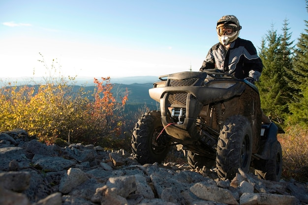 Man riding atv up rocky hill