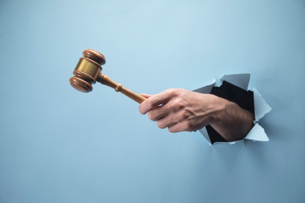 Man's hand holding juge marteau sur scène bleue