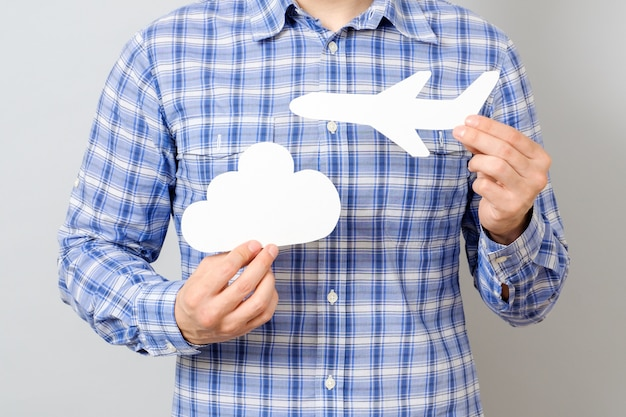 Man's hand holding white paper model of plane and cloud