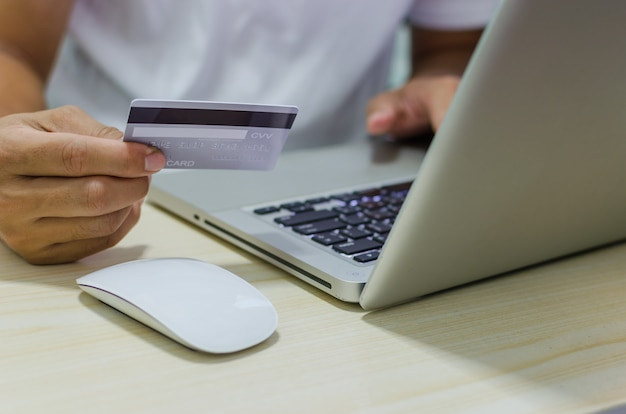 Man shopping en ligne à l'aide d'un ordinateur portable avec carte de crédit