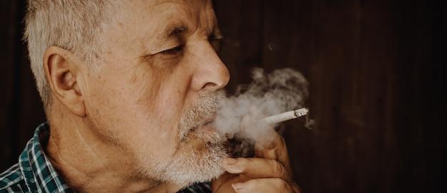 Man smoking cigarette à l'extérieur, la dépendance à la cigarette, mauvaise habitude