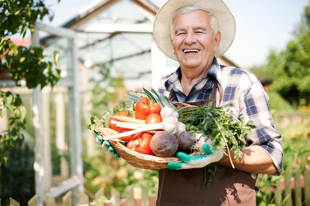 Man travaillant dans le domaine avec une poitrine de légumes