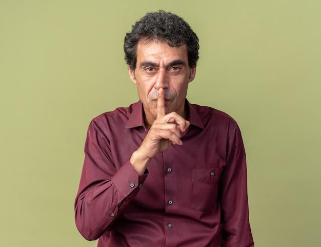 Man en violet regardant la caméra avec un visage sérieux faisant un geste de silence avec le doigt sur les lèvres debout sur le vert