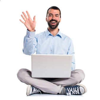Man with laptop saluting