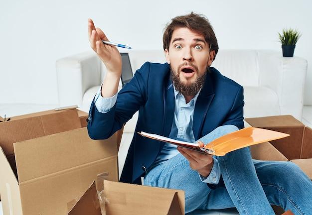 Manager avec des boîtes en carton assis sur le sol déplaçant des objets bureau