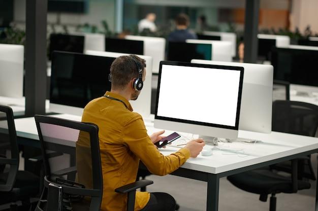 Manager dans les écouteurs travaille sur ordinateur, bureau informatique