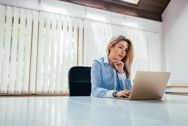 Manager femme blonde songeur regardant un ordinateur portable dans le bureau lumineux. espace de copie.