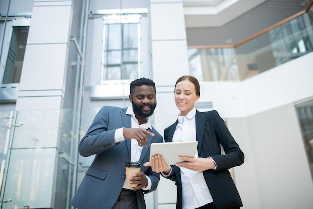 Manager noir positif avec une tasse de café pointant sur la tablette tout en discutant du plan de vente avec un collègue