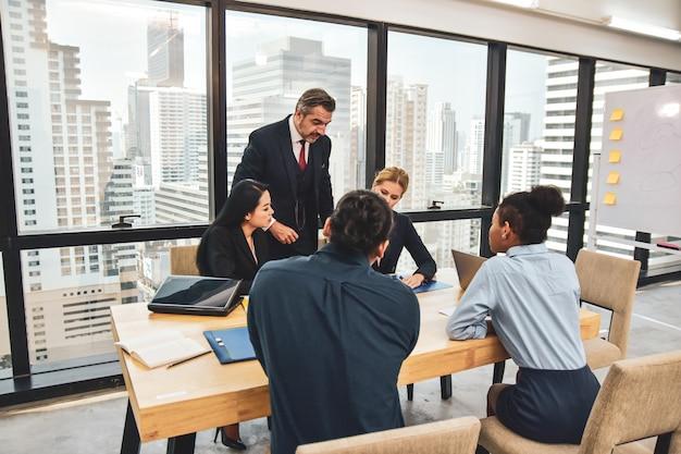 Manager rencontre une équipe commerciale planifiant le marketing d'entreprise vers le succès