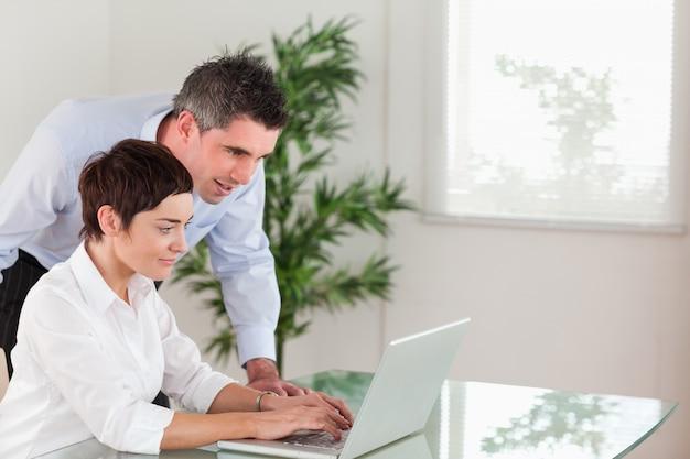 Manager et sa secrétaire travaillant avec un ordinateur portable