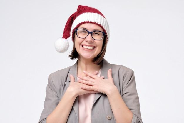 Manager woman in red santa hat est touché par le compliment