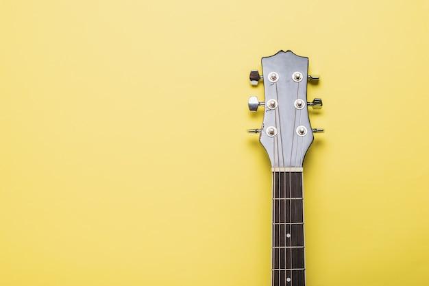 Le manche d'une guitare classique à six cordes sur une surface jaune