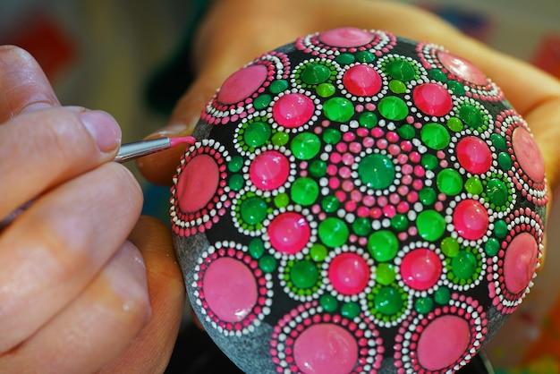 Mandala peint à la main sur pierre avec pinceau