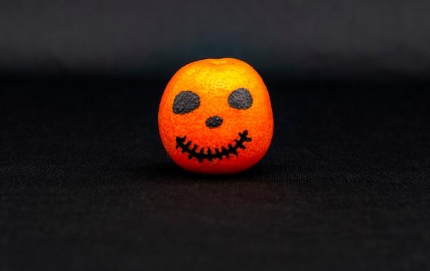 Un mandarin orange peint comme une citrouille d'halloween