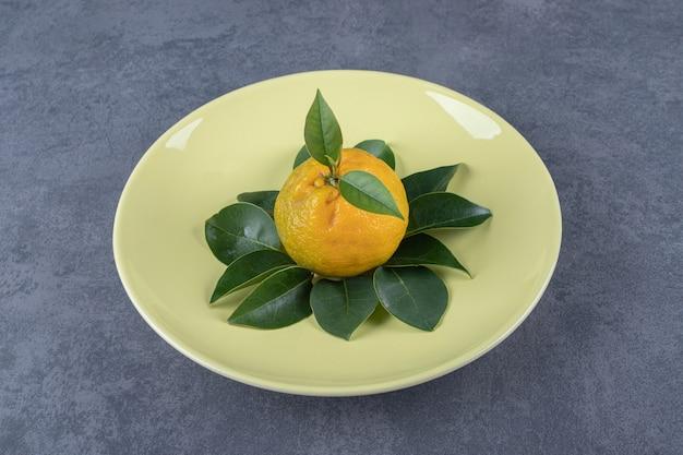 Mandarine biologique fraîche avec des feuilles sur plaque jaune.