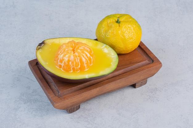 Mandarine biologique fraîche pelée et entière sur planche de bois.