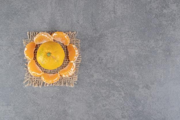 Mandarine entière et segments sur fond de marbre. photo de haute qualité