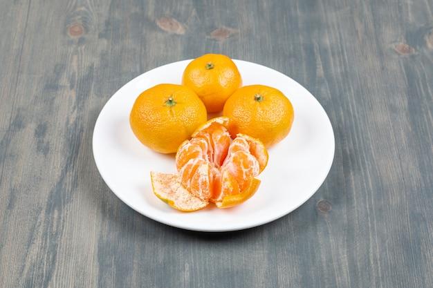 Mandarine épluchée avec des mandarines entières sur plaque blanche