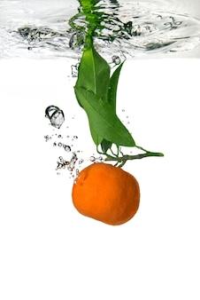 La mandarine est tombée dans l'eau avec des bulles sur blanc