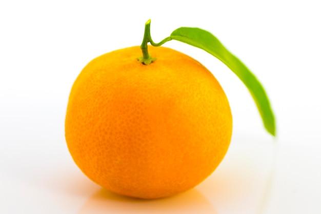 Une mandarine avec feuille sur fond blanc.