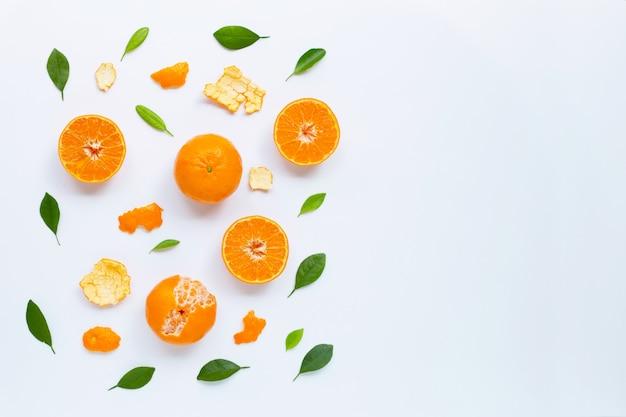 Mandarine fraîche avec des feuilles sur fond blanc