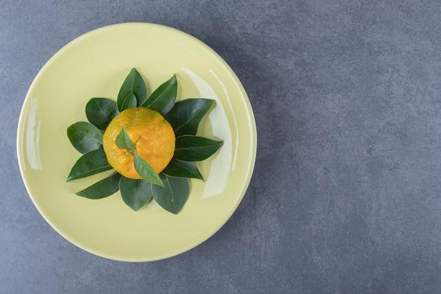 Mandarine fraîche et feuilles sur plaque jaune.