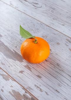 Mandarine fraîche avec des feuilles sur une table en bois