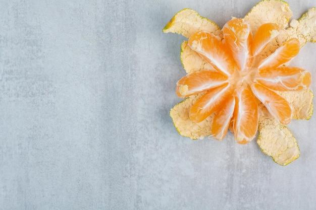 Mandarine fraîche pelée sur fond de pierre. photo de haute qualité