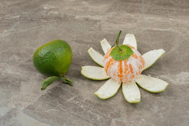 Mandarine fraîche pelée sur marbre.