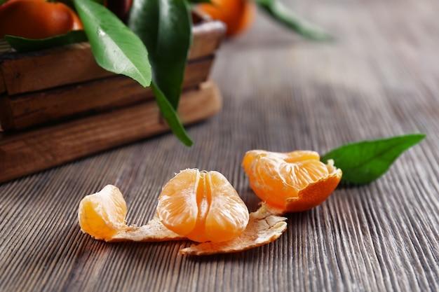 Mandarine fraîche pelée sur table en bois, gros plan