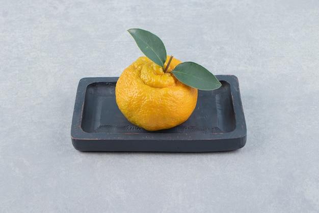 Mandarine fraîche unique avec des feuilles sur plaque noire.