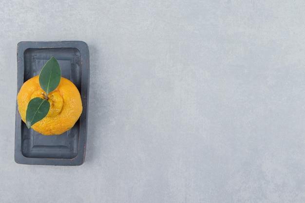 Mandarine fraîche unique avec des feuilles sur plaque noire