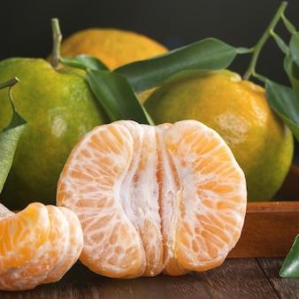 Mandarine mandarine verte fraîche avec des feuilles fraîches sur fond de table en bois foncé concept de récolte.