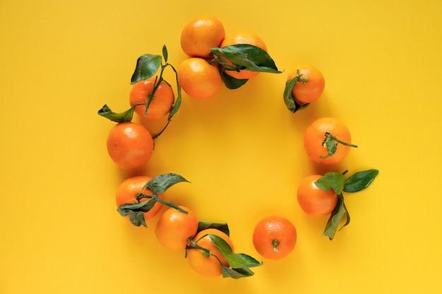 Mandarine orange avec des feuilles o une surface jaune