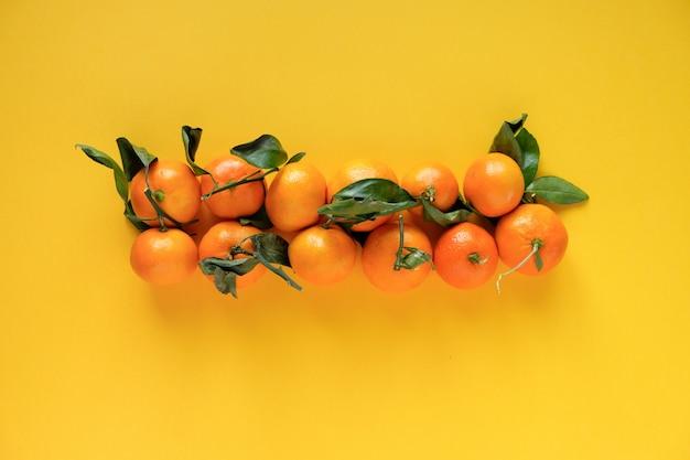 Mandarine orange avec des feuilles sur une surface jaune