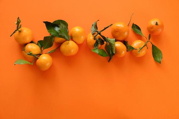 Mandarine orange avec des feuilles sur une surface orange