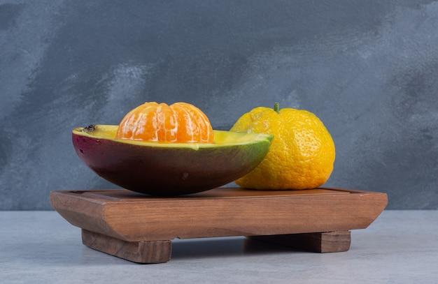Mandarine pelée et entière avec du jus et sur planche de bois.