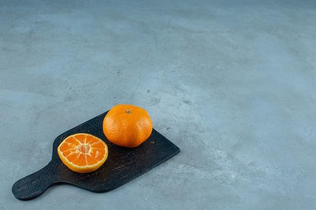 Mandarine tranchée et entière sur une planche à découper , sur le fond de marbre. photo de haute qualité