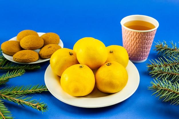 Mandarines sur une assiette blanche, branches de sapin, verre rose et biscuits sur fond bleu.