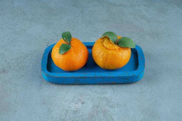 Mandarines biologiques sur une plaque en bois , sur le fond de marbre. photo de haute qualité