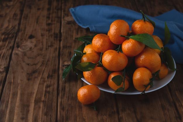 Mandarines cerises avec des feuilles dans une assiette sur une table en bois. photo horizontale avec espace de copie.