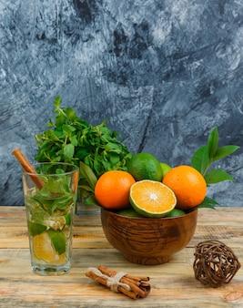 Les mandarines dans un bol avec boisson fermentée et cannelle sur marbre bleu et planche de bois
