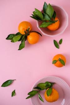 Mandarines dans un bol rose sur une surface rose