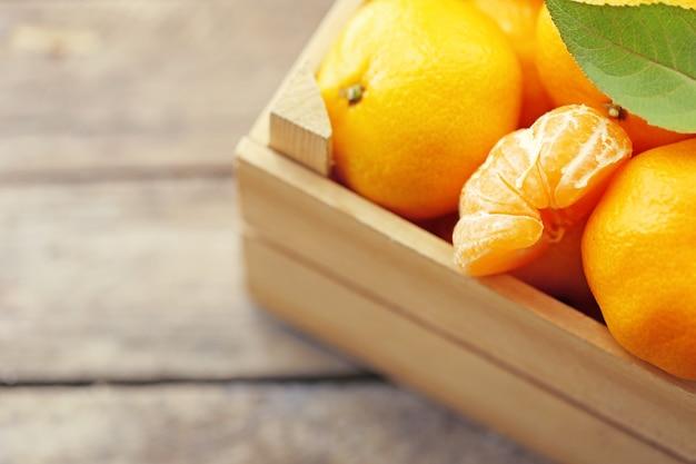 Mandarines dans une caisse en bois, sur une vieille table en bois, gros plan