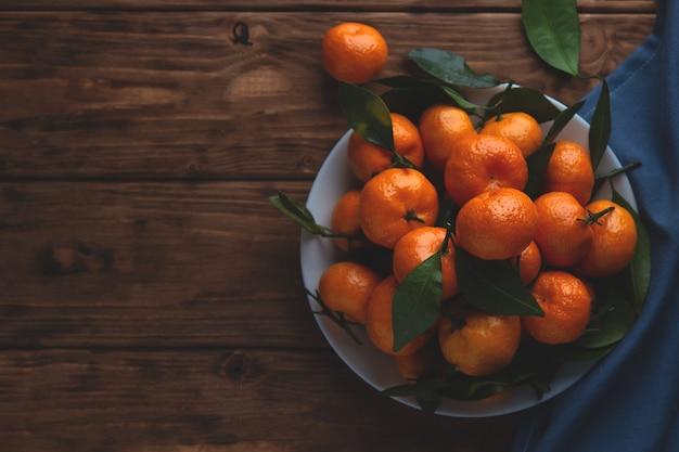 Mandarines avec des feuilles dans une assiette sur un fond en bois.