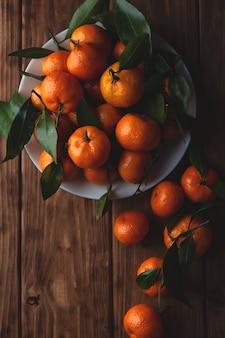 Mandarines avec des feuilles dans une assiette sur une table en bois.