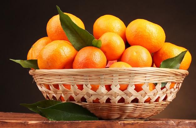 Mandarines avec des feuilles dans un beau panier sur table en bois sur fond marron