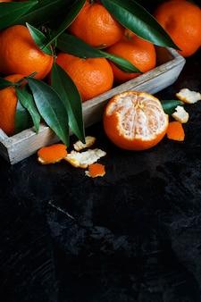 Mandarines avec des feuilles dans une boîte sur un fond sombre